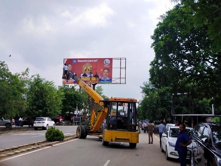 VIP के बैनर-पोस्टर को जेसीबी की मदद से उतरवाती पुलिस।
