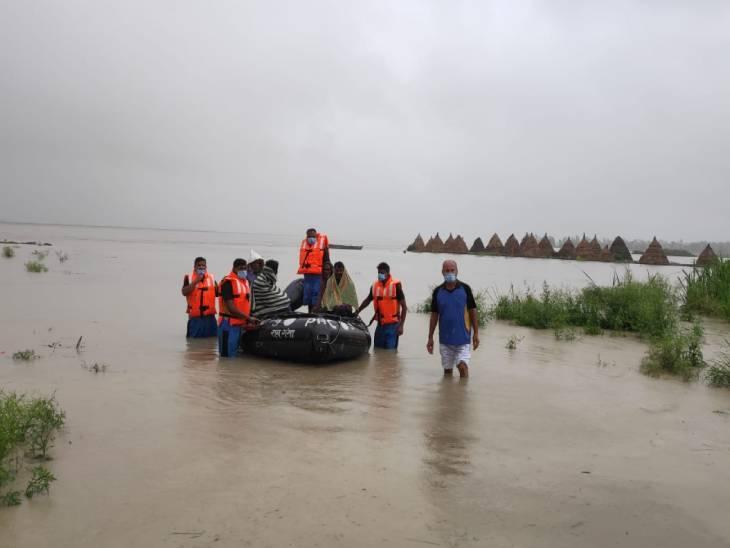 उत्तर प्रदेश के महाराजगंज जिले में नाव से लोगों को ले जा रहा बचाव दल।