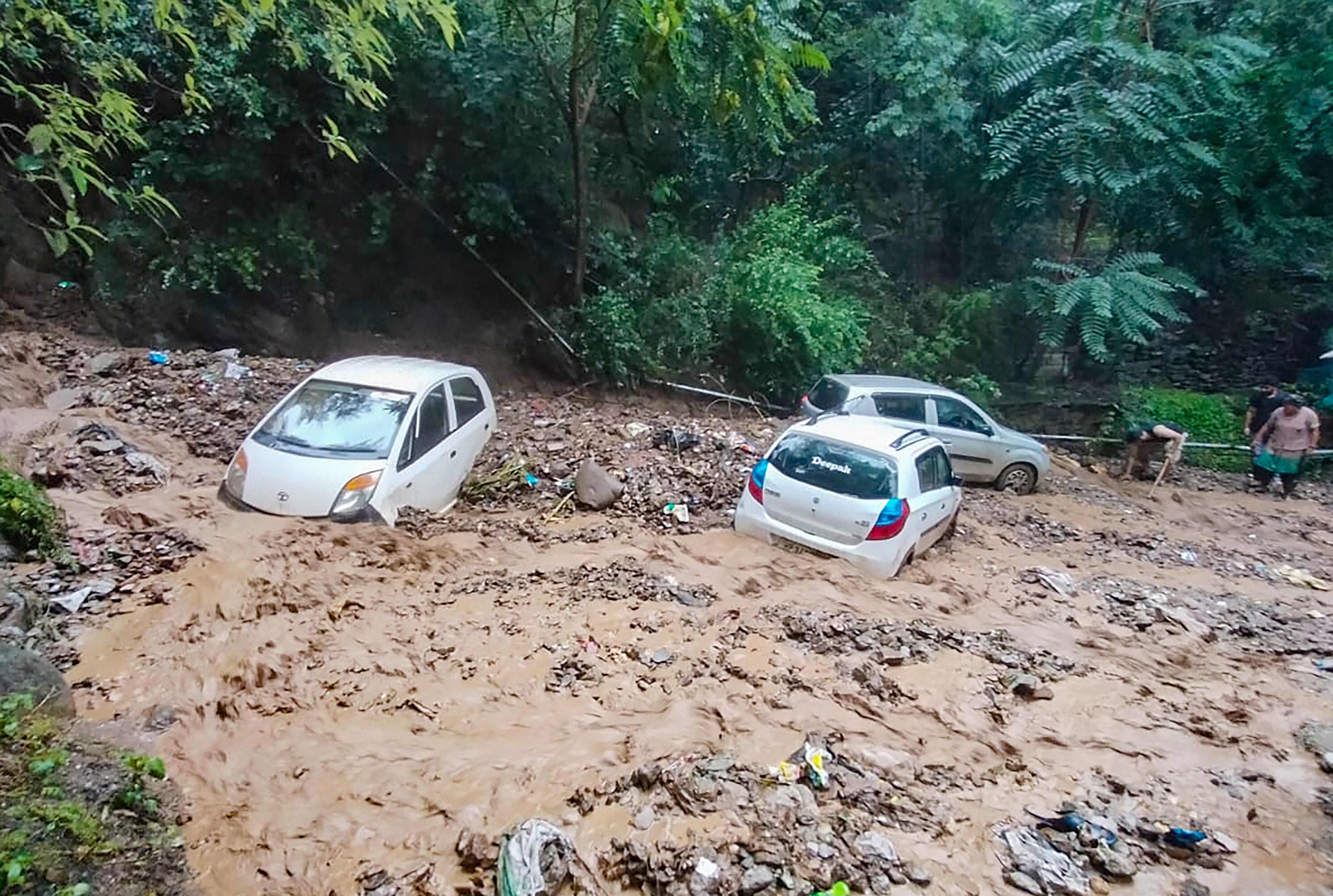 हिमाचल के कुल्लु में बारिश के बाद कारें कीचड़ में फंस गईं।