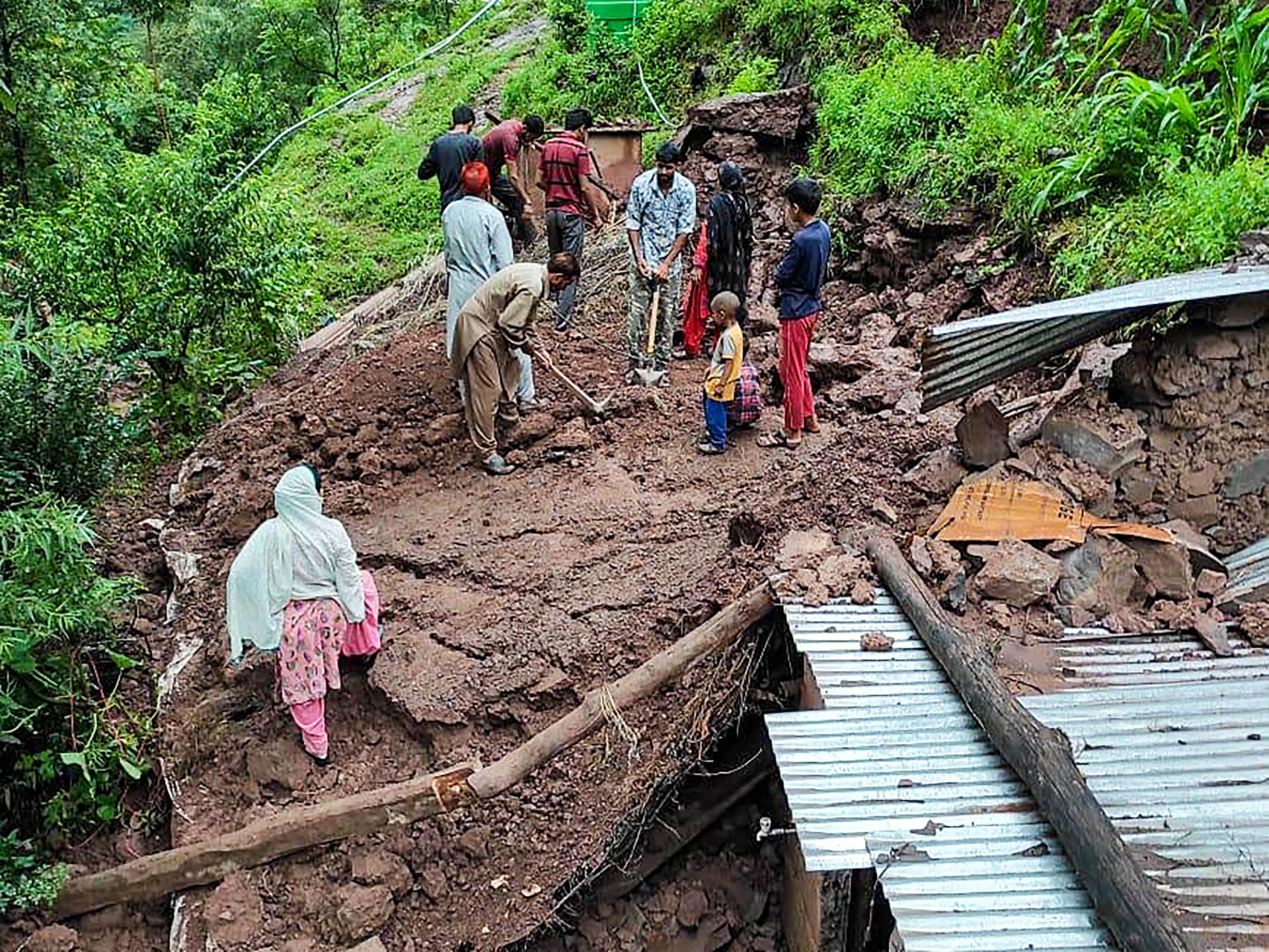 जम्मू-कश्मीर के पुंछ में लैंड स्लाइड के बाद तबाह हुए घर से मलबा हटाता परिवार।