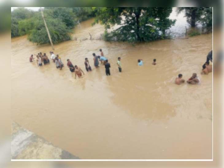 बरवा नदी के रपटा पुल पर आए पानी में निकलते हुए लोग।