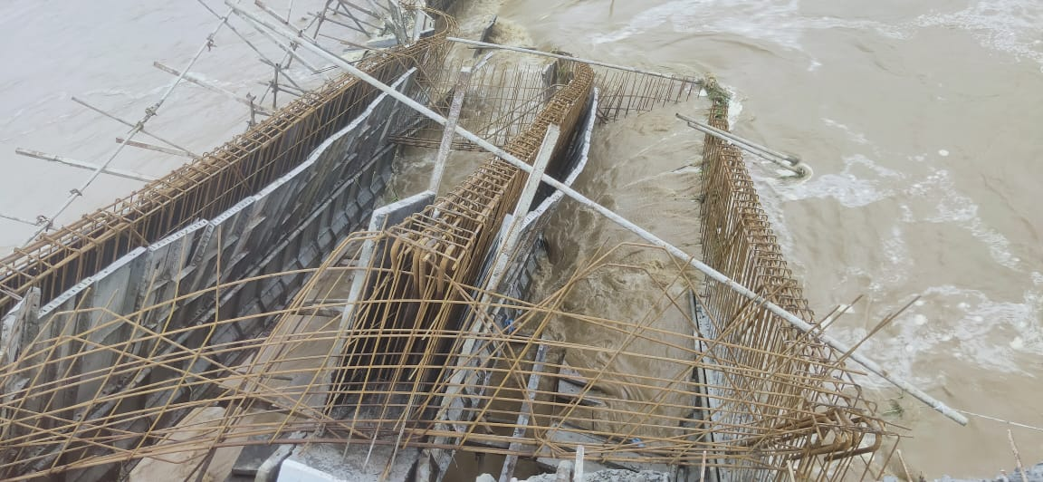 मामूली बाढ़ के बाद इस पुल के ऊपर रखे जाने वाले स्लैब नदी में गिर गए।