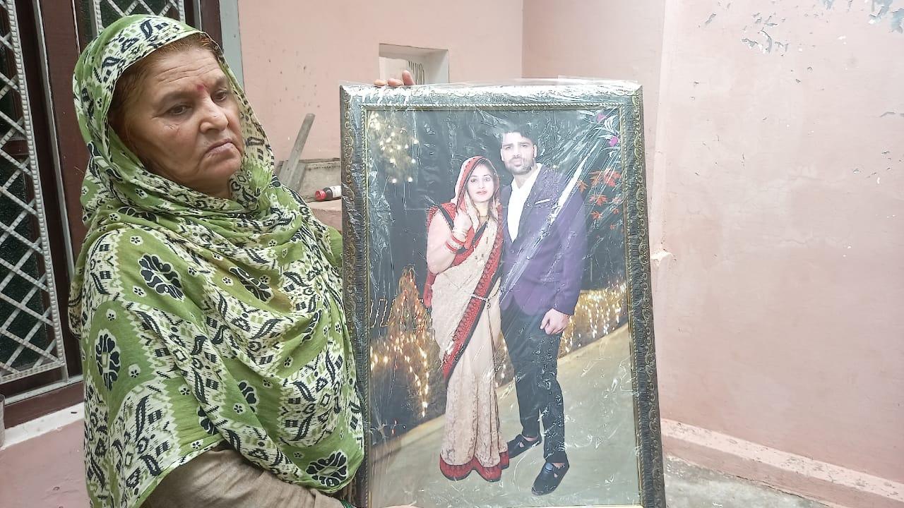 सतीश यादव की मां गुड्डी अपने बेटे और बहू की फोटो के साथ।