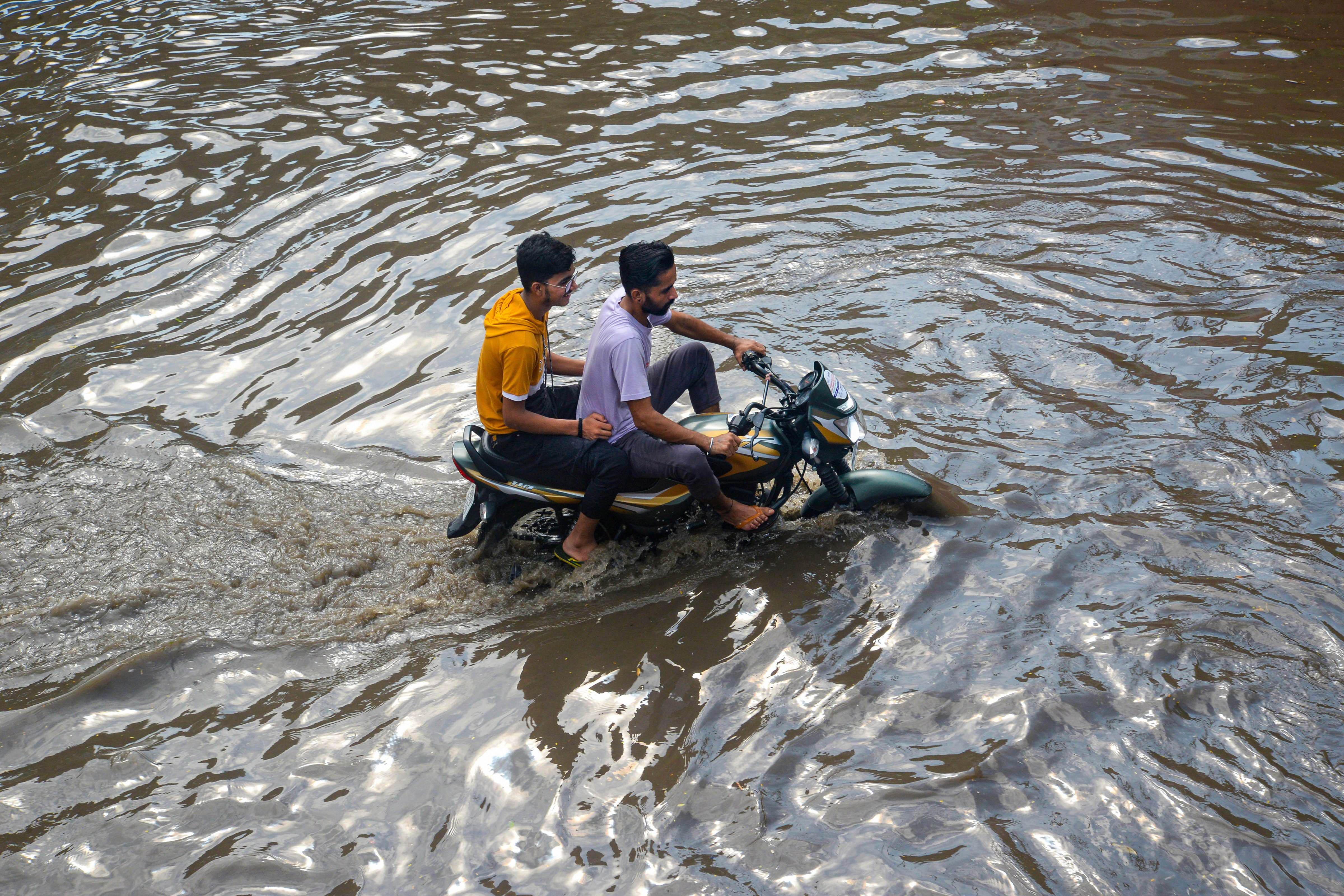पंजाब के जालंधर में सड़क पर पानी भरने के बाद बाइक से गुजरते युवक।