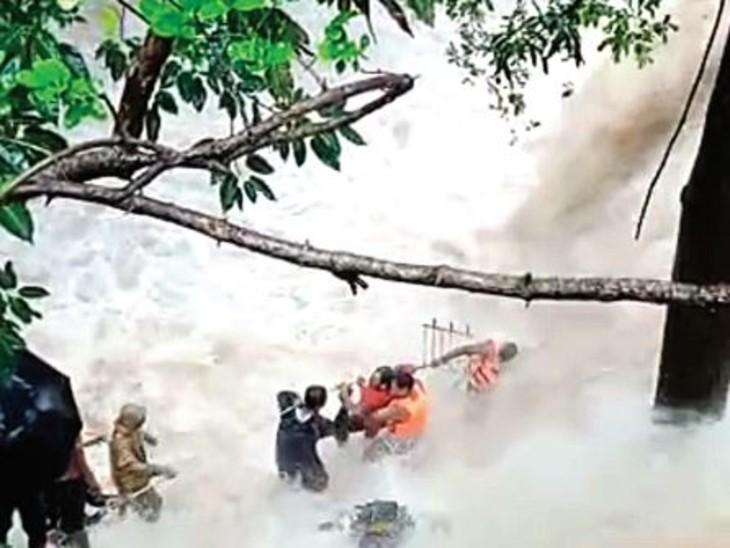 शिवपुरी के भदैयाकुंड झरने में बहे युवक को बचाते गोताखोर।