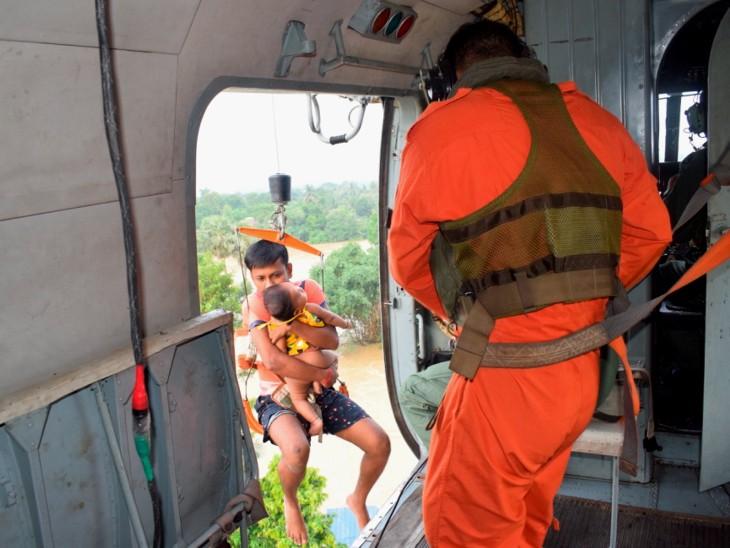 हुगली जिले के खानकुल इलाके में बाढ़ में फंसे एक परिवार को रेस्क्यू करते एयरफोर्स के जवान। सोमवार को 31 लोग एयरलिफ्ट किए गए।