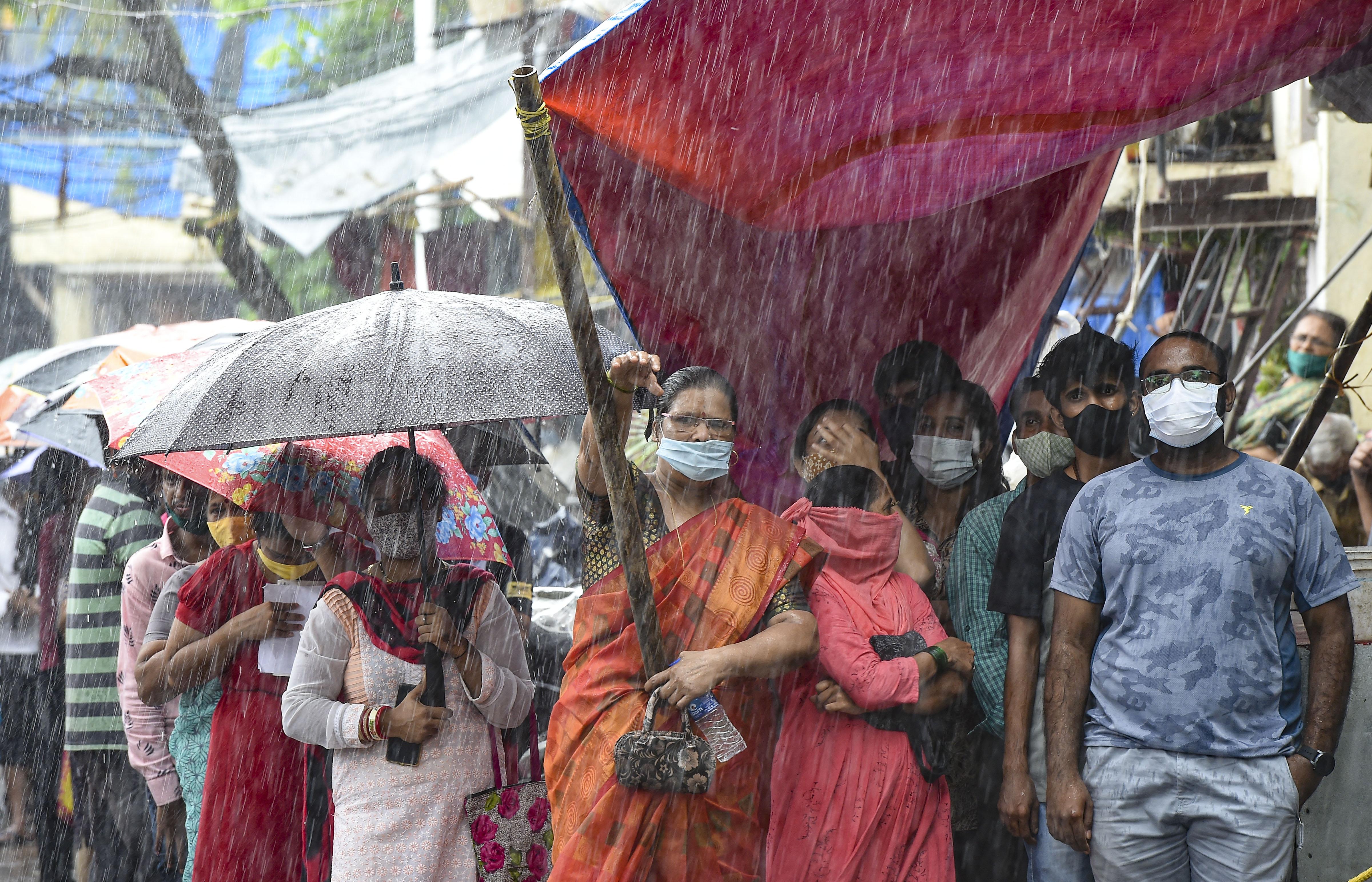 फोटो मुंबई की है। यहां बारिश के बावजूद लोग वैक्सीन लगवाने पहुंच रहे हैं। वैक्सीनेशन के बढ़ते दायरे के बावजूद देश में कोरोना के हर दिन 30 हजार से ज्यादा केस आ रहे हैं।