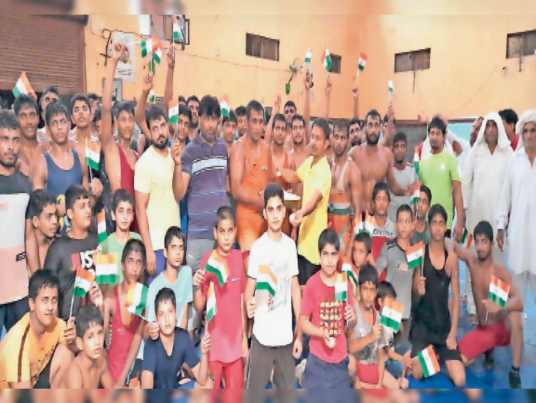 गांव छारा के वीरेंद्र अखाड़ा के पहलवान बजरंग पूनिया की जीत पर तिरंगा लहरा कर खुशी मनाते हुए। - Dainik Bhaskar