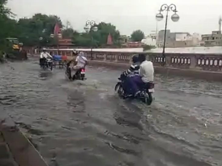 बीकानेर में हुई तेज बारिश के बाद सूरसागर रोड पर भरे पानी के बीच से गुजरते वाहन।