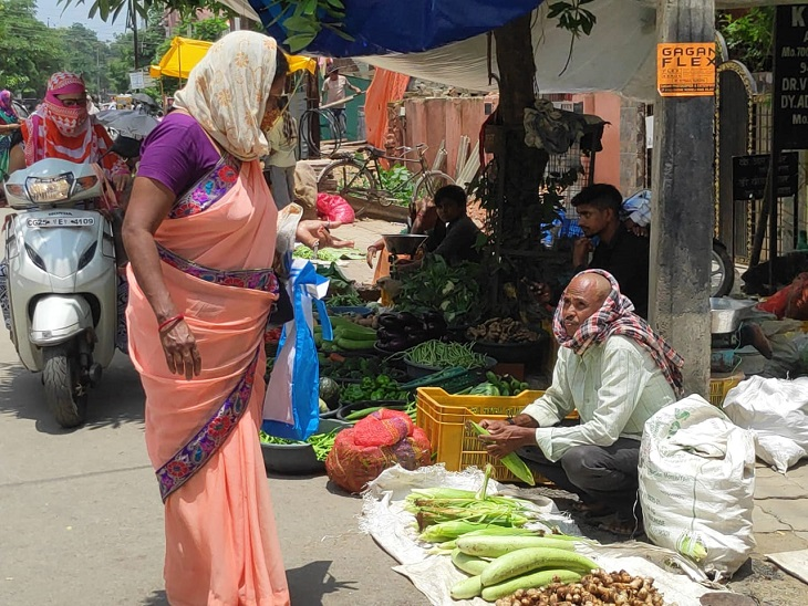 चिलचिलाती धूप में बैठकर सब्जी बेचता व्यापारी।