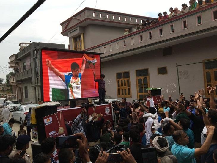 आलिंपिक में गोल्ड जीतने के बाद नीरज के गांव में जश्न मनाते लोग।