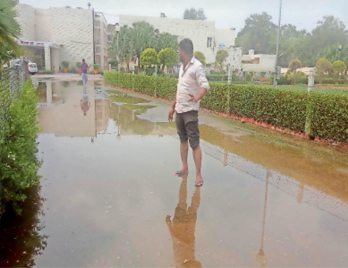 जलभराव के बीच से निकलते कर्मचारी। - Dainik Bhaskar