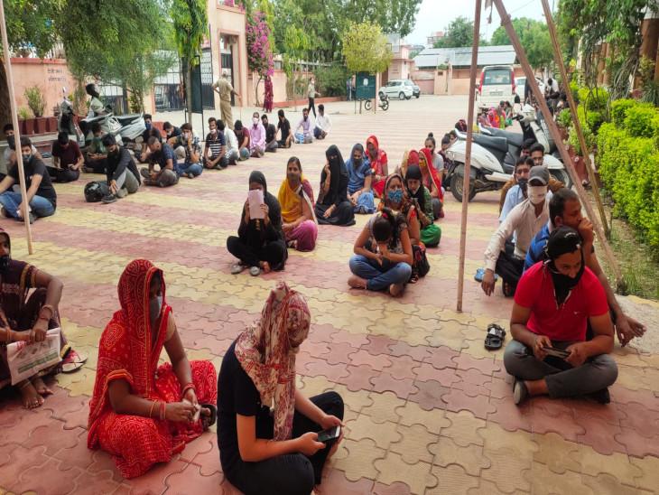 एसके कॉलेज में वैक्सीन का इंतजार करते हुए बैठे लोग