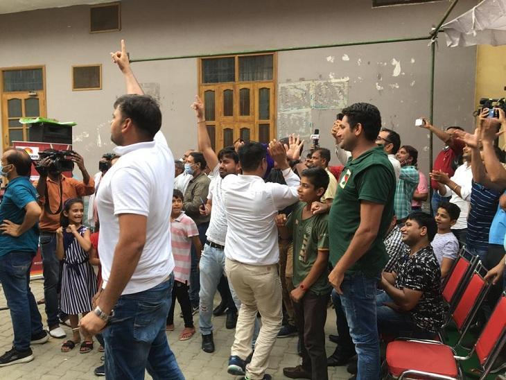 नीरज चोपड़ा की जीत पर उनके घर में जश्न मनाते हुए लोग।