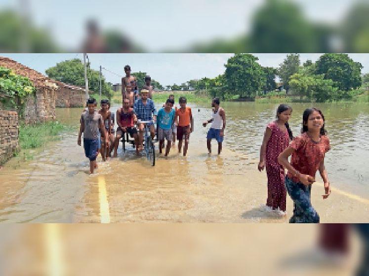 बाढ़ के पानी में सड़क डुब जाने के कारण ठेला गाड़ी के सहारे सड़क पार करते ग्रामीण। - Dainik Bhaskar