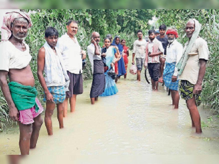 सड़कों पर फैले बाढ़ के पानी को पारकर घर को जाते बाढ़ से घिरे गांव के ग्रामीण। - Dainik Bhaskar