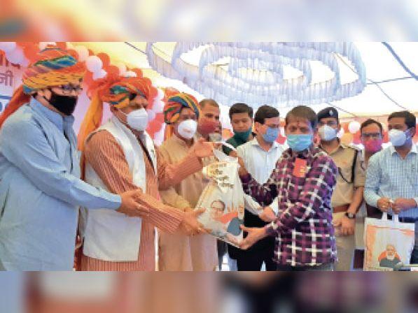 तलेनी गांव में कार्यक्रम में निशुल्क राशन देते मंत्री डॉ यादव व अन्य। - Dainik Bhaskar