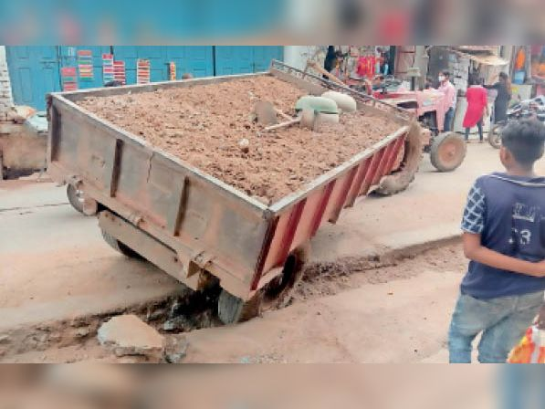 सड़क के बीच फंसी रेत की ट्रॉली। - Dainik Bhaskar