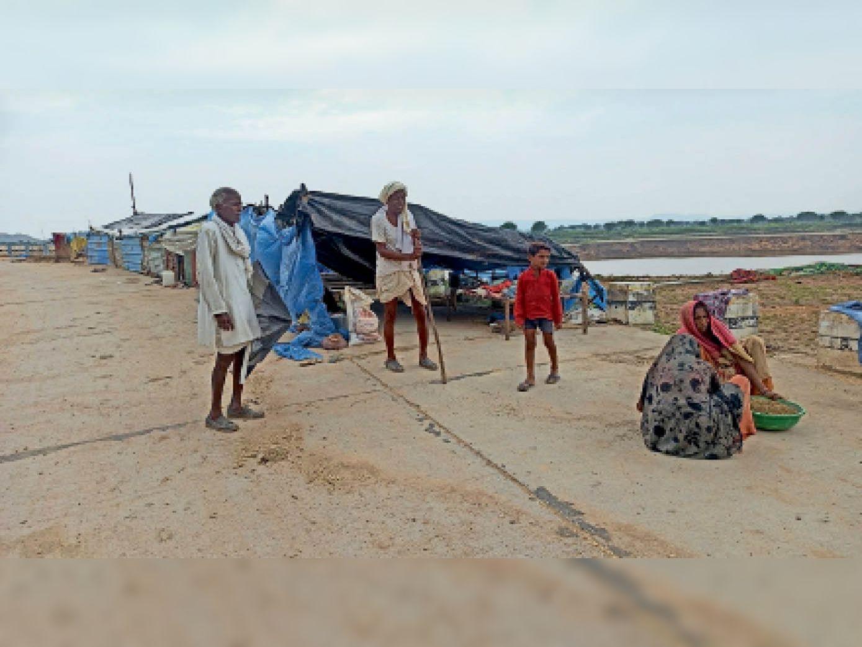 गांव उजड़ने के बाद अब सड़क किनारे तिरपाल की झोपड़ी बनाकर रह रहे ग्रामीण। - Dainik Bhaskar