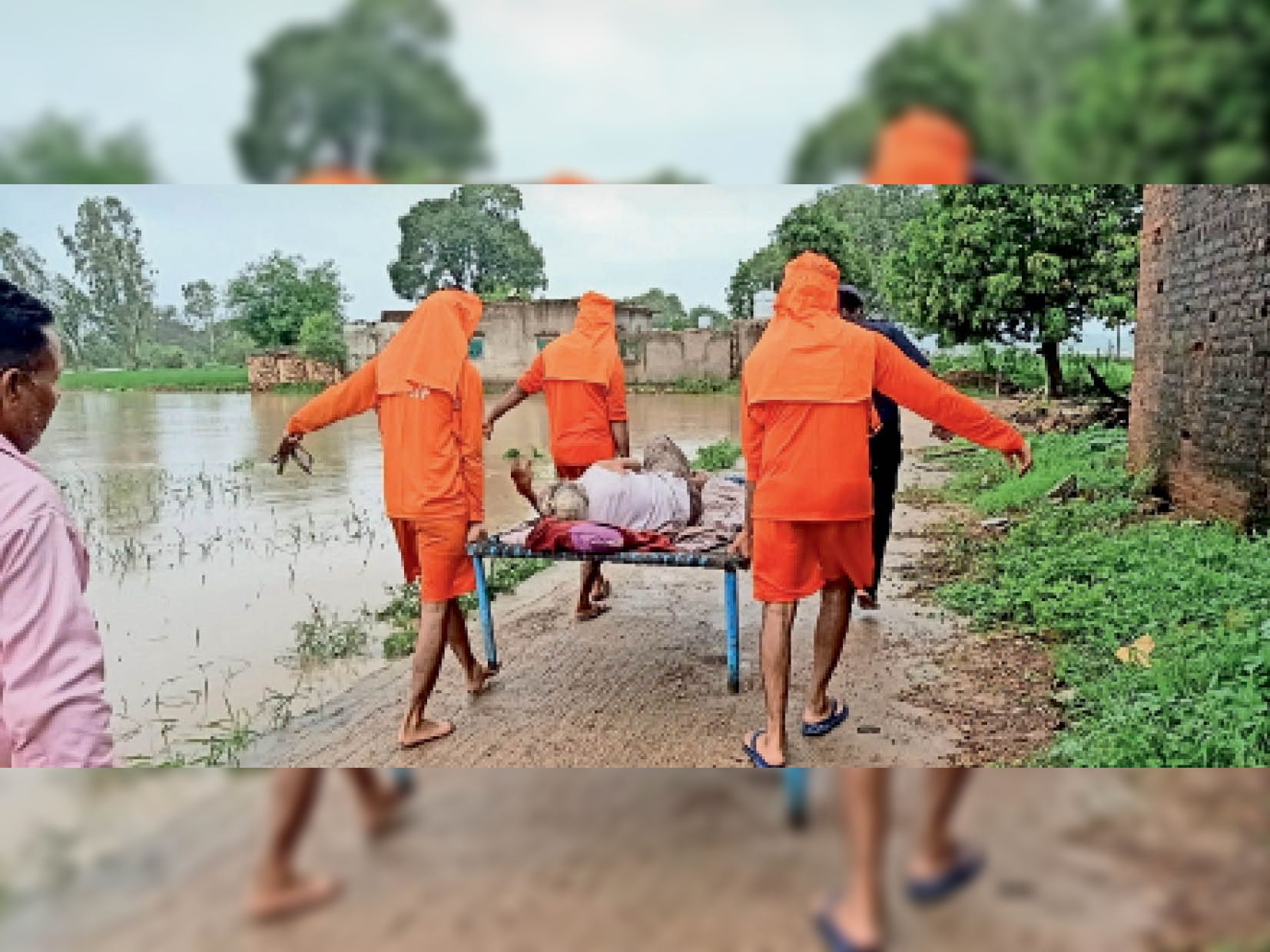 चलने-फिरने में असमर्थ बुजुर्ग को खटिया सहित सुरक्षित स्थान पर ले जाते टीम के जवान। - Dainik Bhaskar