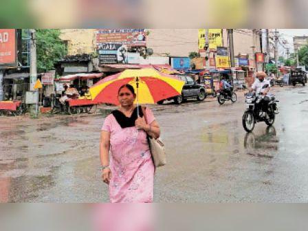 नवांशहर में नेहरू गेट पर बारिश के दौरान छाता लेकर गुजरती महिला। - Dainik Bhaskar