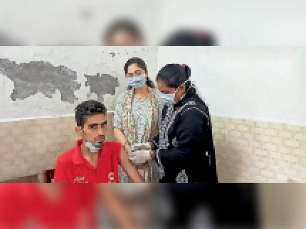 कैंप में युवक के वैक्सीन लगाती सेहत विभाग की टीम। - Dainik Bhaskar