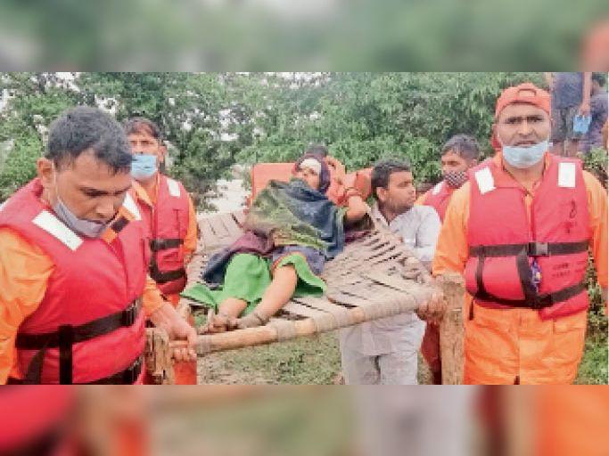 छबड़ा. सुंडा गांव में रेस्क्यू ऑपरेशन के दौरान प्रसूता को खाट पर लिटाकर लाते एनडीअारएफ के जवान। - Dainik Bhaskar