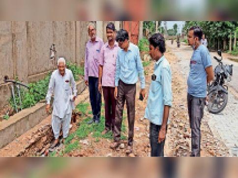 लालसोट  औद्योगिक क्षेत्र में पानी निकासी के नाले में हो रही अनियमितताओं व दरकती दीवारों की जानकारी देते उद्यमी। - Dainik Bhaskar