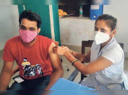 कोरोना रोधी टीका लेते युवक। - Dainik Bhaskar
