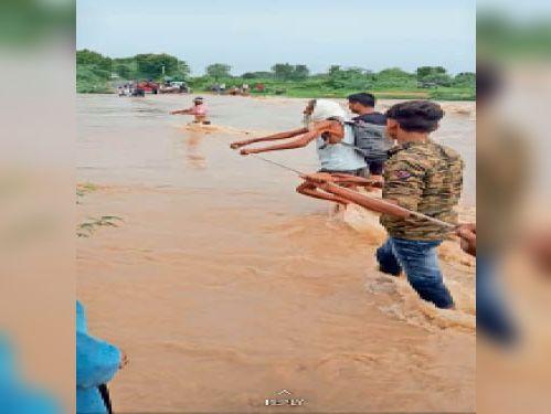 बनेठा  टोंक मार्ग पर नाला उफान पर आने के बाद भी रस्सी बांधकर नाला पार कराते युवक। - Dainik Bhaskar