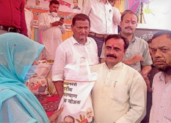 अन्न उत्सव के तहत अनाज का थैला बांटते राज्यमंत्री। - Dainik Bhaskar