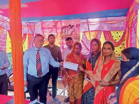 बैंक ऑफ बड़ौदा में आयोजित क्रेडिट कैंप में लाभुकों को चेक देते अधिकारी। - Dainik Bhaskar