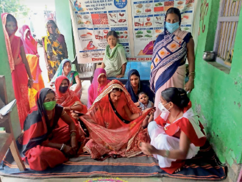 खोदावंदपुर में गर्भवती महिला की गोद भराई करती सेविका। - Dainik Bhaskar