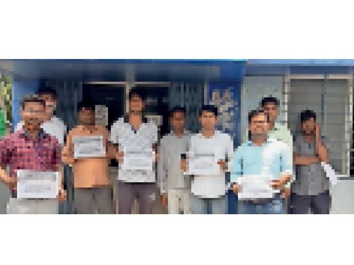 बिजली कंपनी के प्रवेश द्वार पर पोस्टर प्रदर्शन करते हड़ताली कर्मचारी। - Dainik Bhaskar