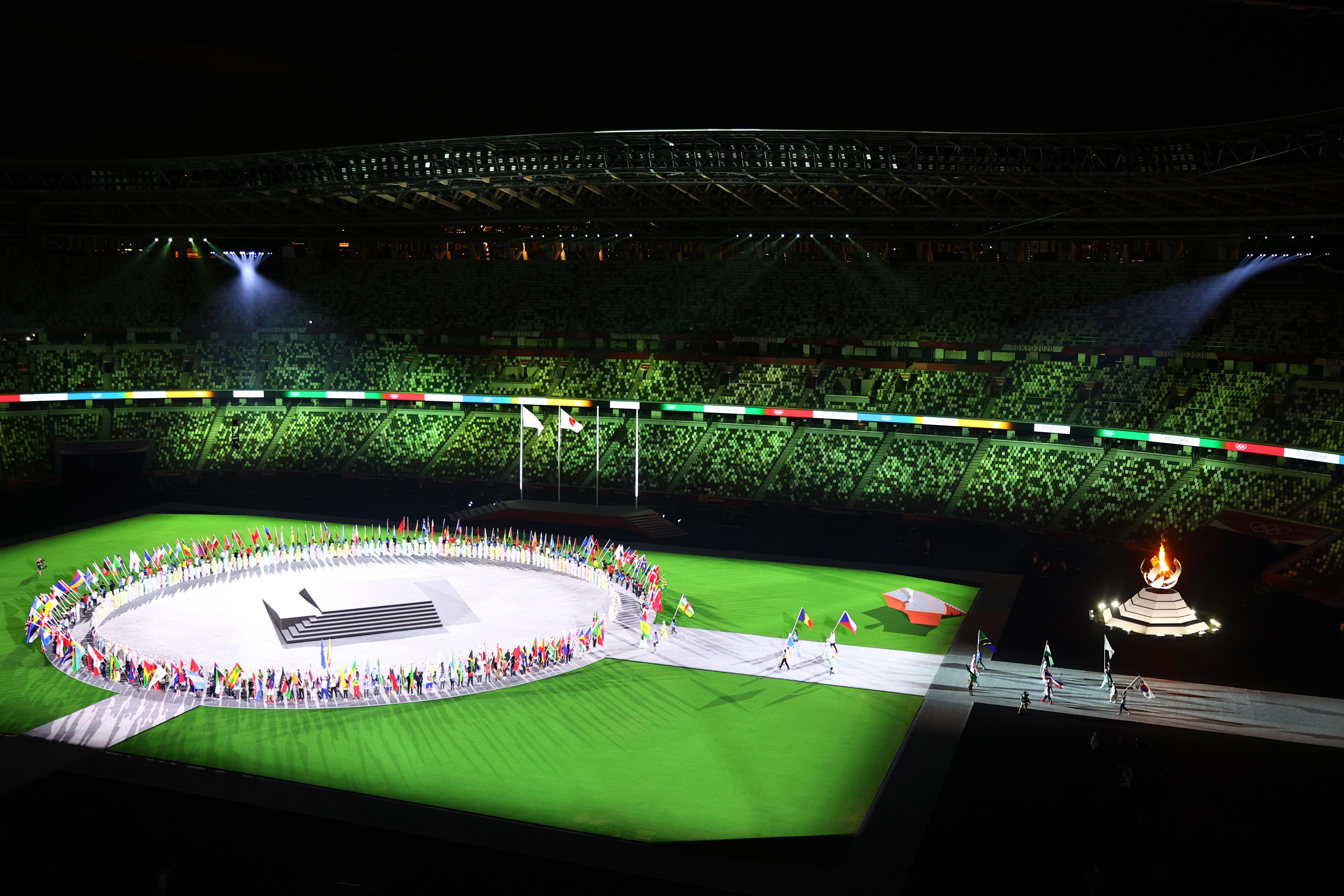 सभी एथलीट्स स्टेडियम में एक गोले में खड़े हैं। बीच में म्यूजिक बैंड स्टेज पर परफॉर्म कर रहे हैं।