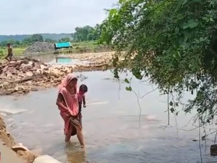 पुल बह जाने की वजह से पानी के बीच नाला पार करती महिला।