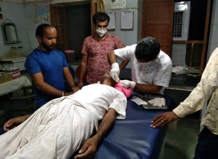 बुजुर्ग के टूटे कानों का उपचार करते चिकित्साकर्मी।