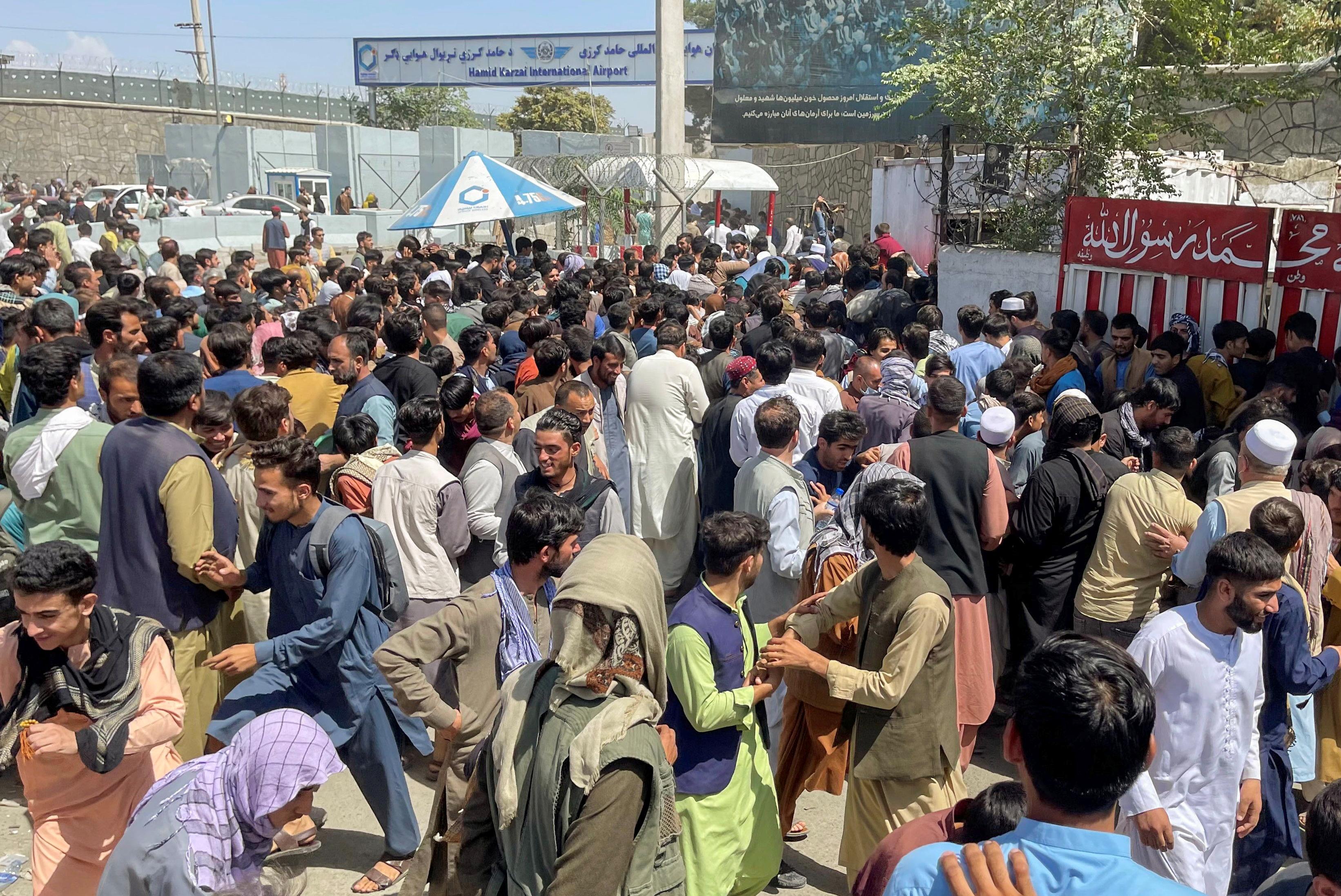 रविवार को तालिबान के काबुल पर कब्जा करने के बाद हामिद करजई इंटरनेशनल एयरपोर्ट पर लोगों की भीड़ बढ़ गई। तस्वीर में एयरपोर्ट के अंदर घुसने की कोशिश करते लोग।