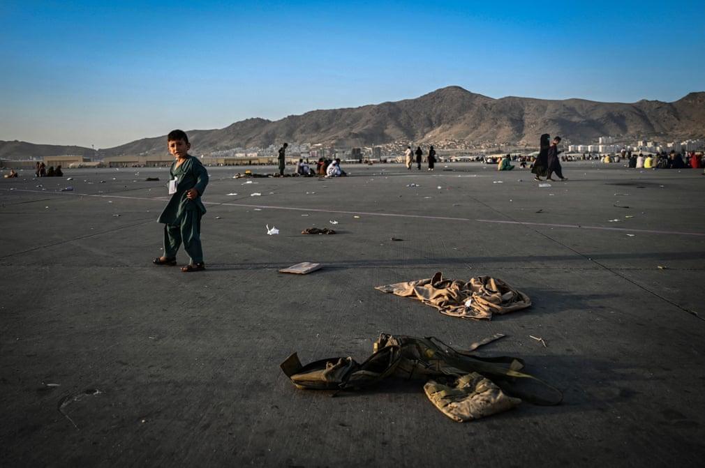 काबुल एयरपोर्ट पर बिखरी पड़ी सेना की वर्दियों बीच से गुजरता एक बच्चा। काबुल एयरपोर्ट पर हजारों की संख्या में लोग विमानों में जगह मिलने का इंतजार कर रहे हैं।