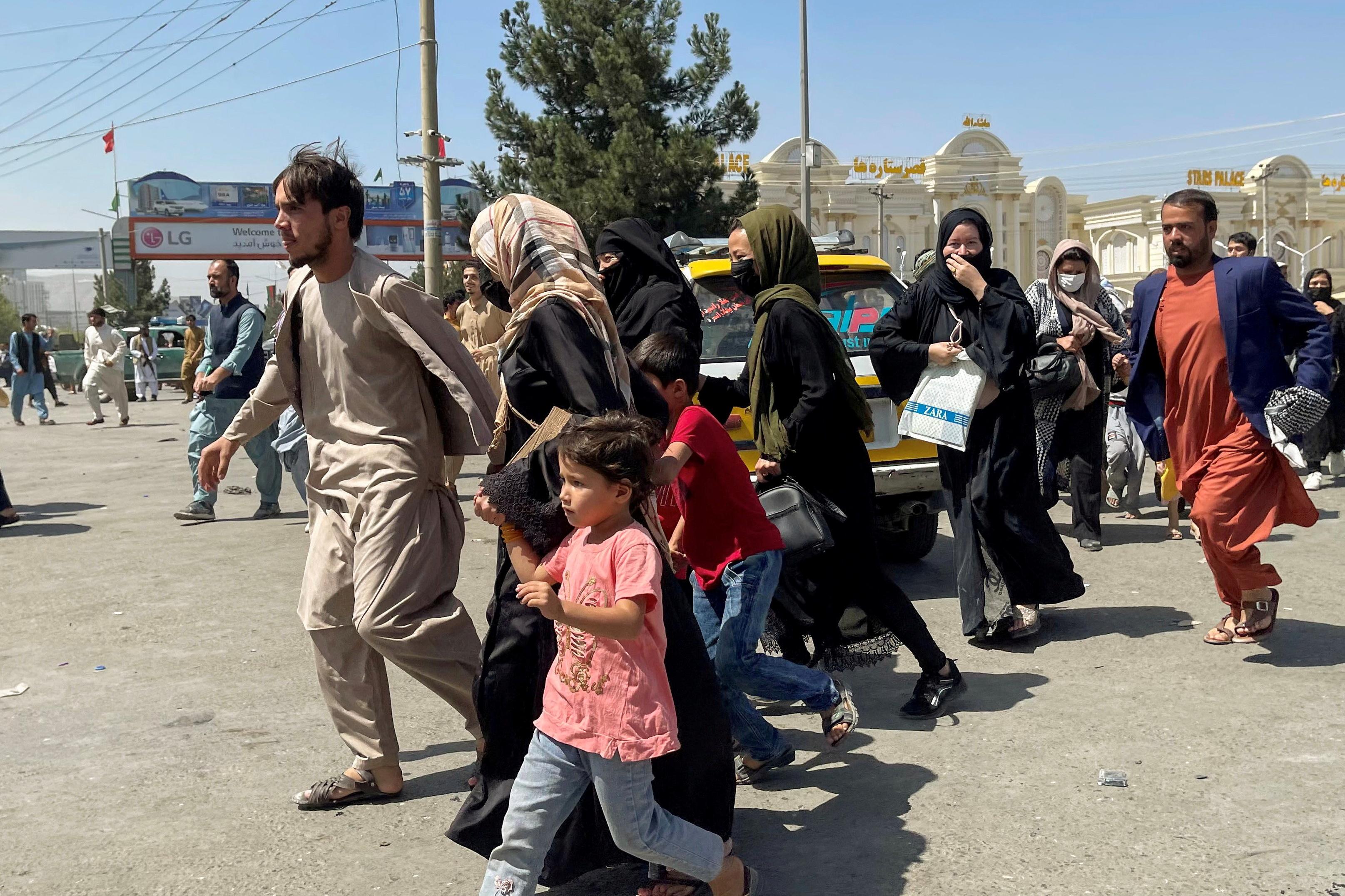 काबुल के हामिद करजई इंटरनेशनल एयरपोर्ट में घुसने के लिए भागते अफगानी।