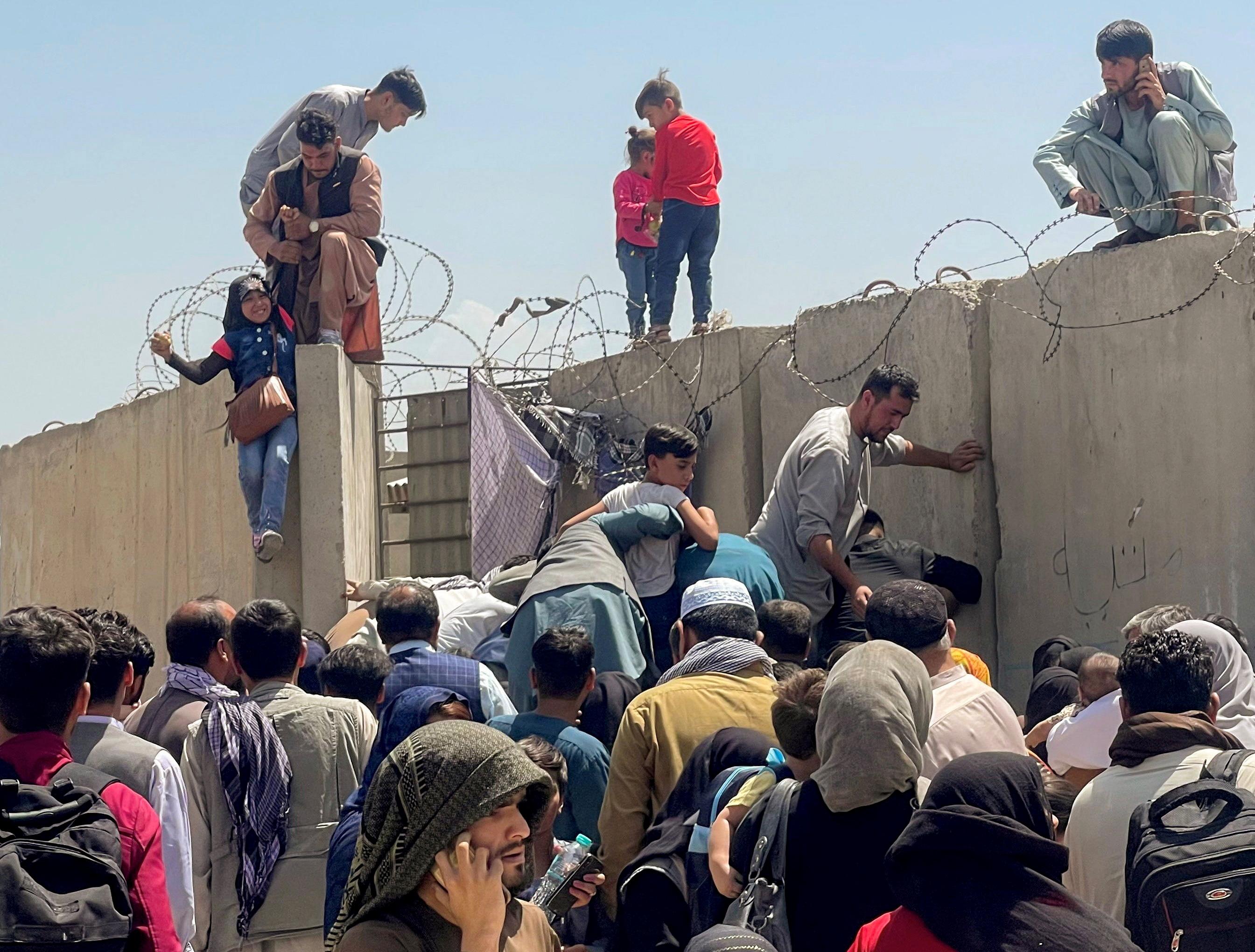 काबुल एयरपोर्ट की दीवार फांदकर अंदर घुसने की कोशिश करते लोग। यहां पर हजारों की संख्या में लोग पहुंचे हुए हैं जो भागने के लिए किसी प्लेन में जगह मिलने का इंतजार कर रहे हैं।