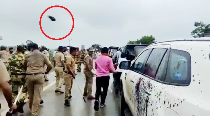 The policemen walking in the convoy of the BJP leader somehow pulled him out of there.  Stone thrown at car in red circle.