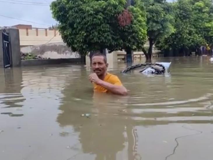 बठिंडा की जलमग्न सड़क में से गुजरता रिक्शा चालक।