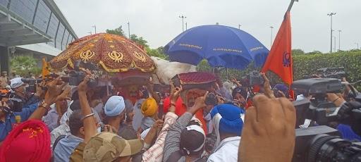 गुरु ग्रंथ साहिब को नगर-कीर्तन के साथ ले जाने के एयरपोर्ट पर सिख समुदाय के लोगों की भारी भीड़ जमा थी।