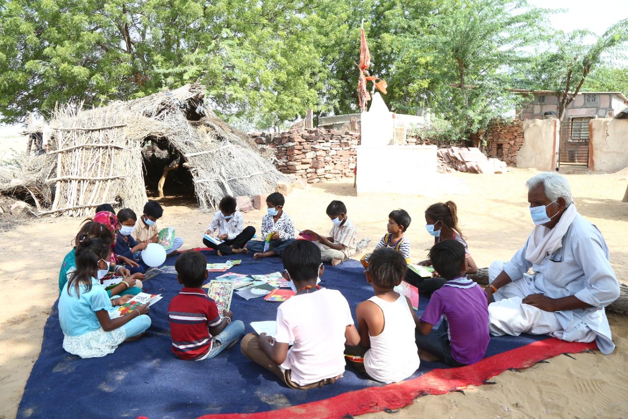 घर के आंगन में बैठकर बच्चों को सुनाई जा रही है कहानियां।