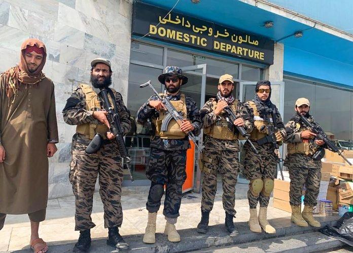 काबुल एयरपोर्ट पर कब्जा होने के बाद डिपार्चर गेट के बाहर फोटो सेशन कराते तालिबानी लड़ाके। ये लड़ाके अफगानी सेना से छीनी गई अमेरिकी मिलिट्री ड्रेस पहने हैं।