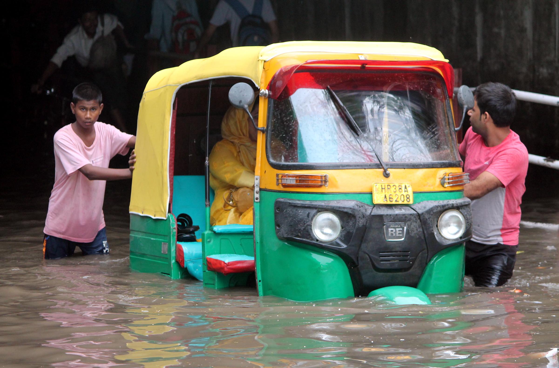 फरीदाबाद में एक अंडरपास में भरे पानी के बीच ऑटो को निकालते लोग।