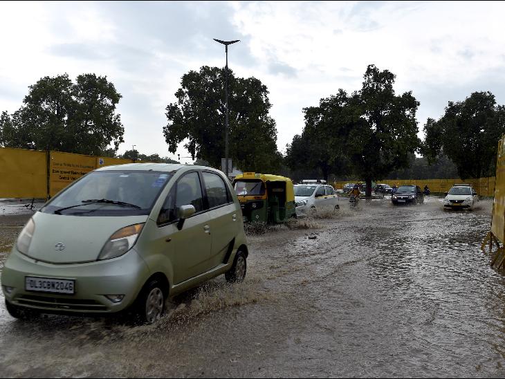 दिल्ली प्रगति मैदान के पास पानी भरी सड़क से गुजरते वाहन।