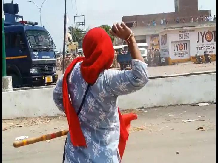 पुलिस की गाड़ी पर पत्थर फेंकती महिला।