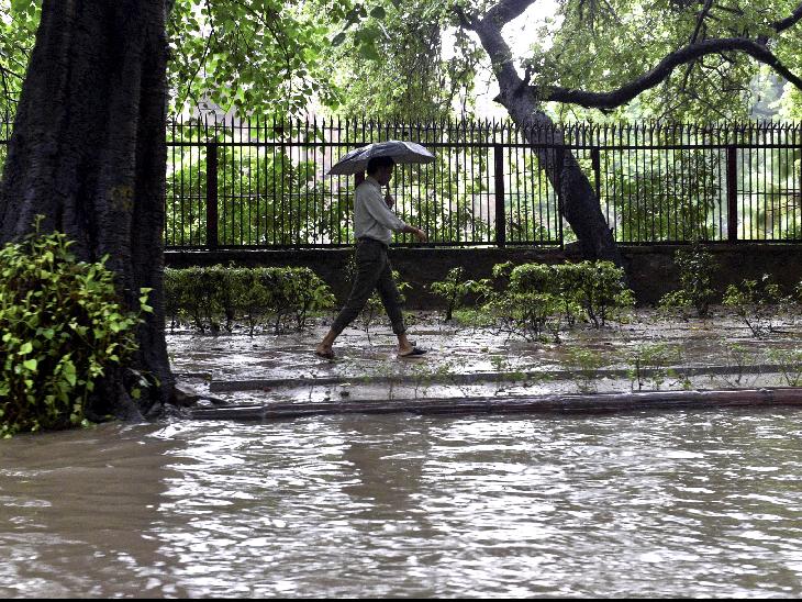 दिल्ली हाईकोर्ट के पास पानी भरी सड़क के पास से गुजरता व्यक्ति।